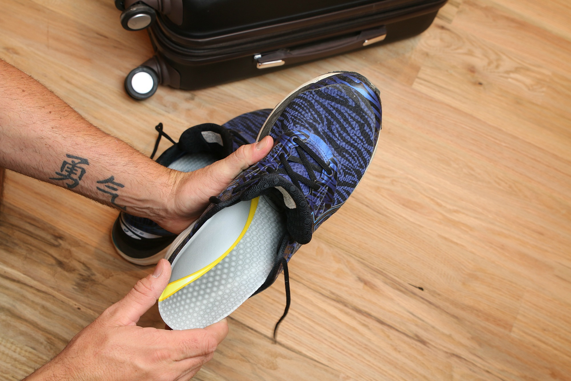 placing insole into tennis shoe