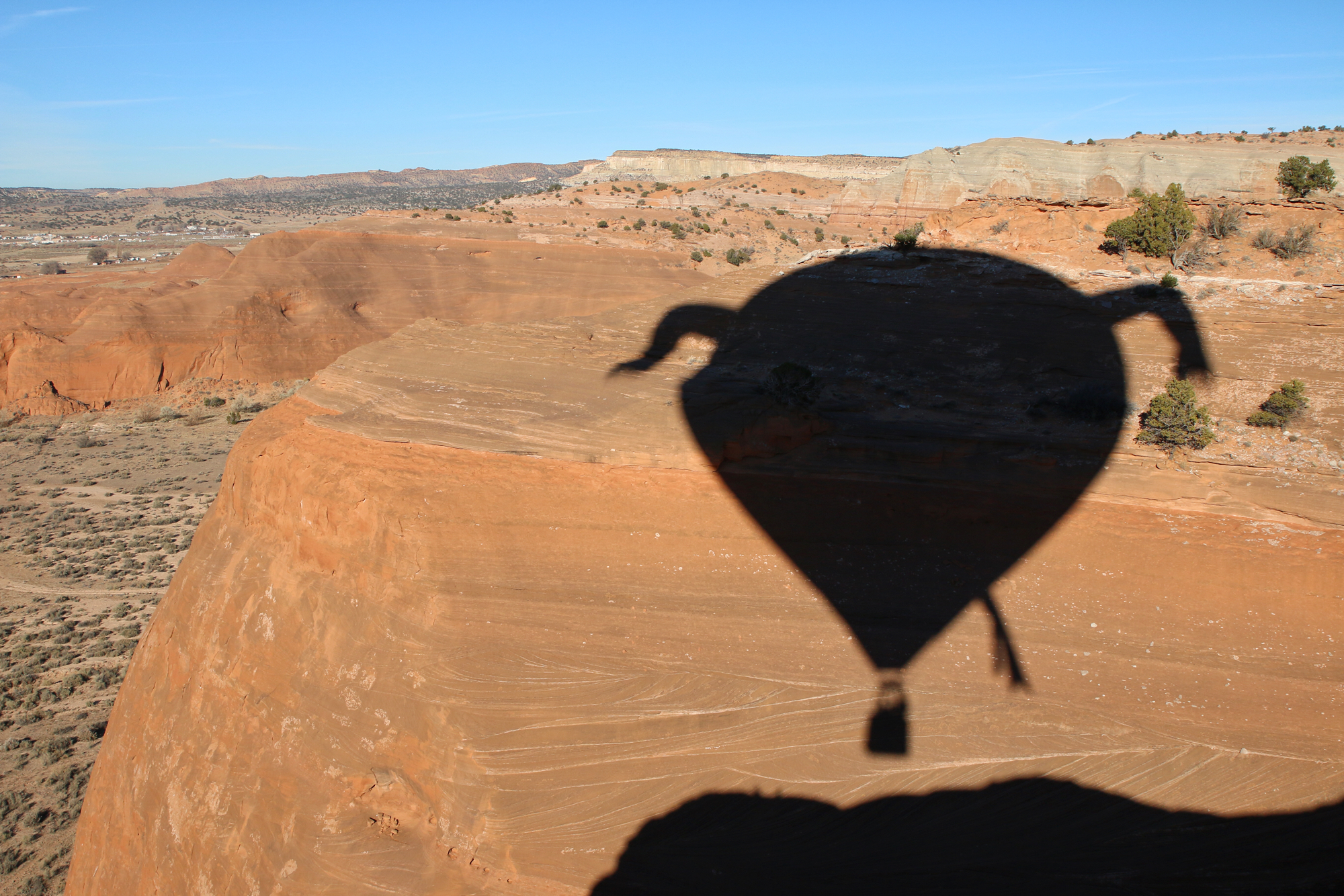 shadow silhouette of hot air balloon on red rocks