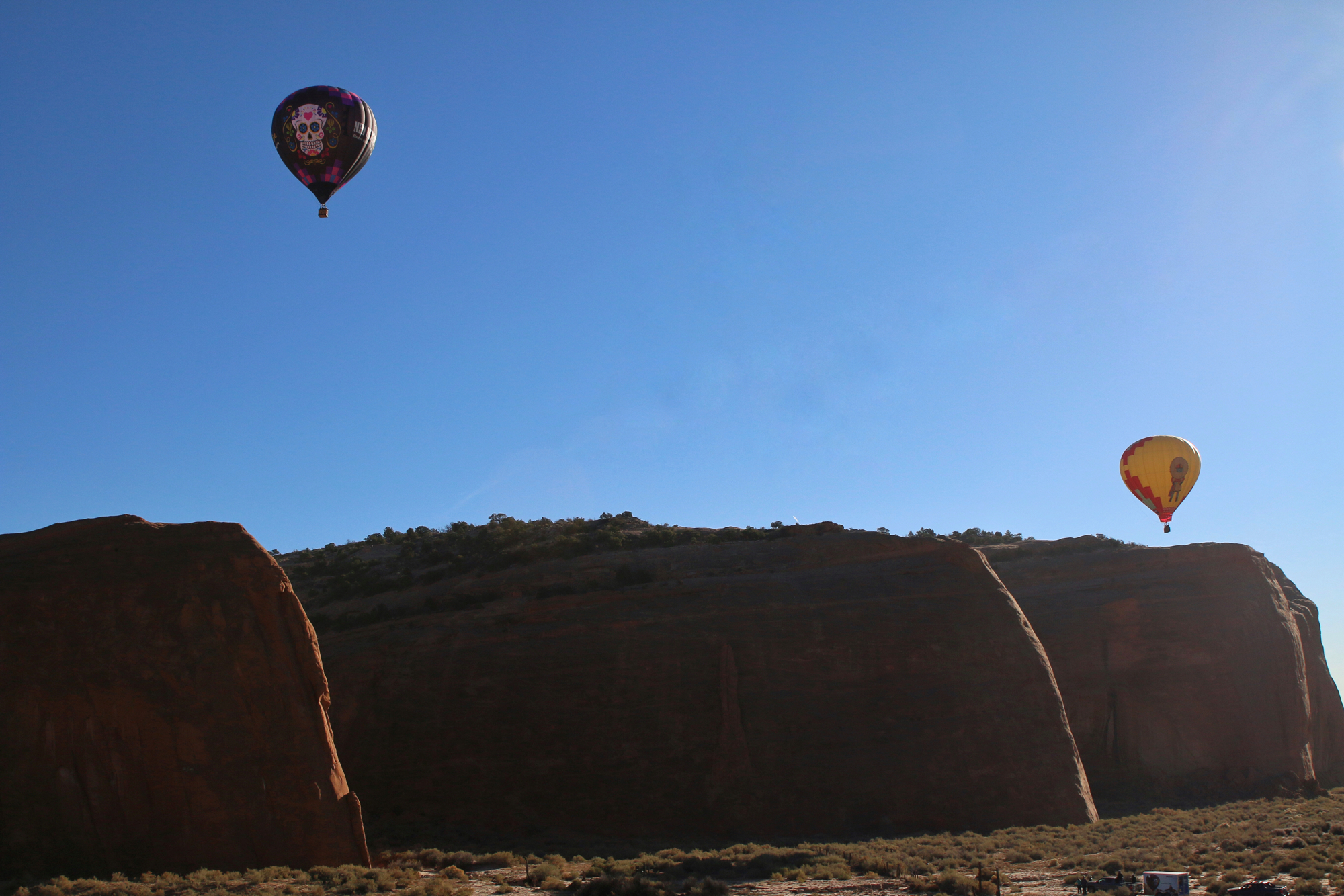 view of other hot air balloons in flight over red rocks